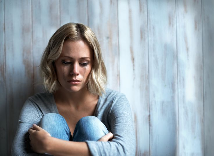 A woman crying because she's in an abusive relationship with an addict.